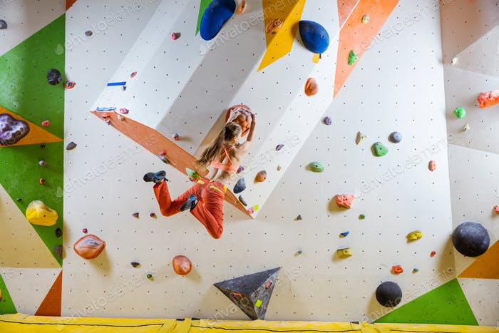 Young athletic woman jumping on climbing hold in bouldering gym