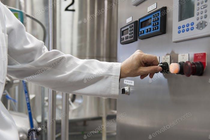 Ein Techniker in weißem Mantel schaltet die Steuerung in Verarbeitungsanlagen in einer großen Abfüllanlage ein.