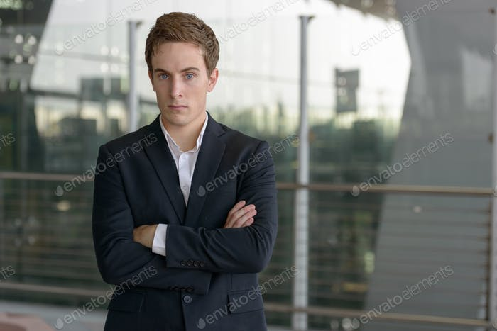 Portrait of young handsome businessman at the airport