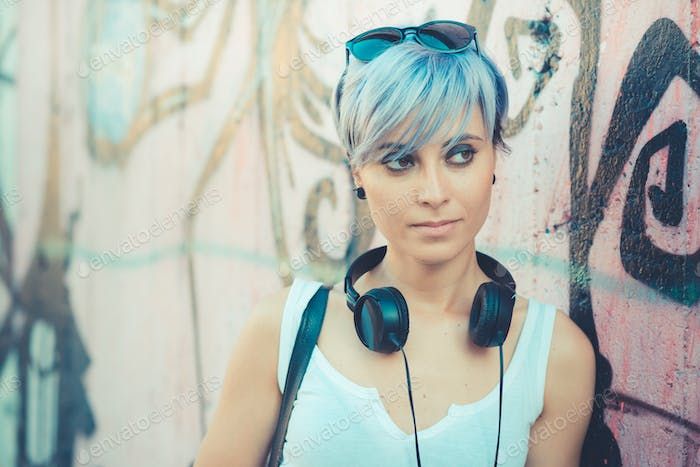 young beautiful short blue hair hipster woman with headphones mu