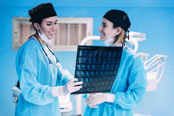 Стоматолог показывает что-то своему коллеге на рентгеновском снимке.