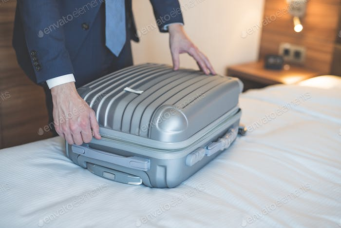 Young businessman with a luggage in the room
