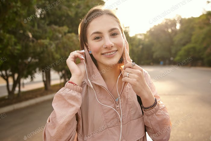 Photo of young positive lady walking at the park, listening music in headphones