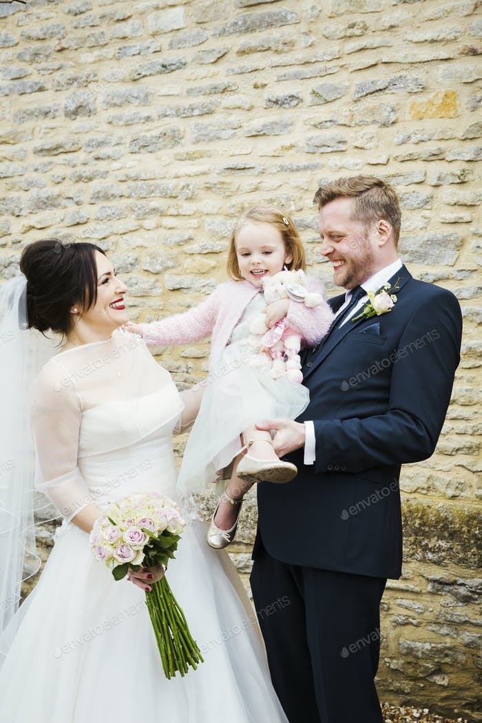 A bride and groom, a couple on their wedding day, holding a young child.