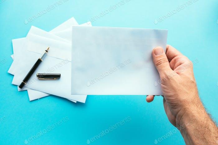 Hand holding blank white envelope