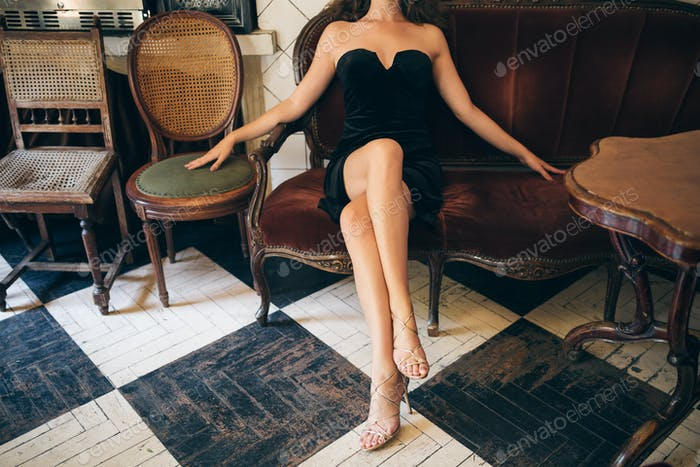 elegant beautiful woman sitting in vintage cafe in black velvet dress