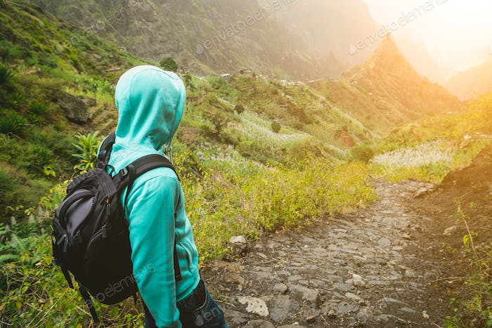Alone traveler with backpack walking down cobbled trekking trail towards green valley. Sun flares on