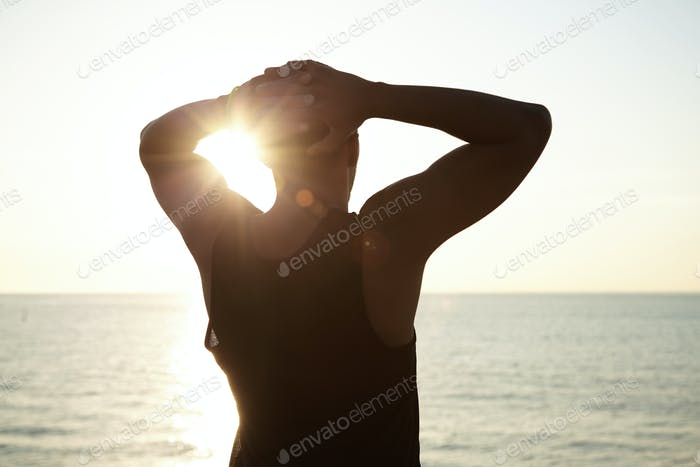Silhouette of young African man wearing sleeveless top clasping hands behind his head, admiring beau