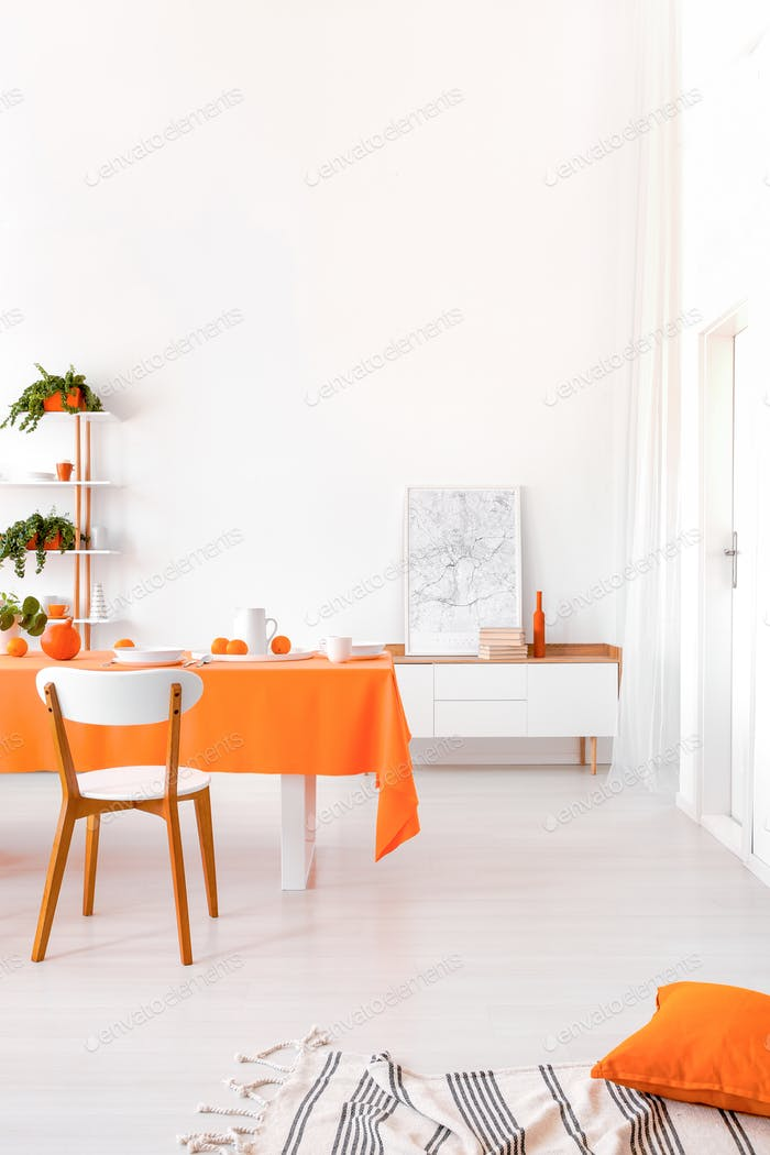 Long table with orange cloth, plates and fruits standing in whit