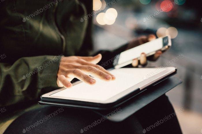 Nahaufnahme auf den Händen der jungen Frau mit Smartphone und Tablet