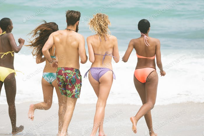 Rear view of multi ethnic group of friends running at beach on sunny day