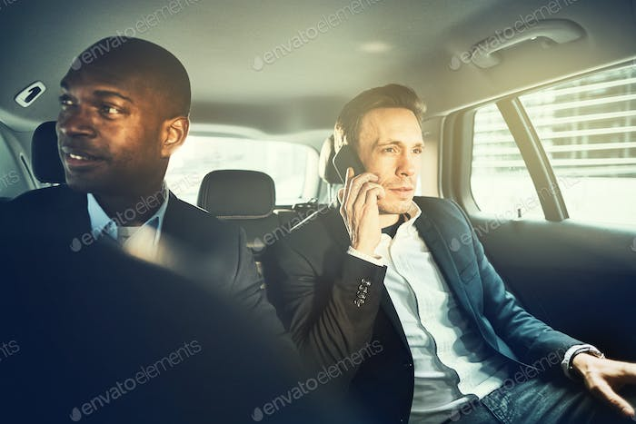 Businessmen sitting in car being driven through the city