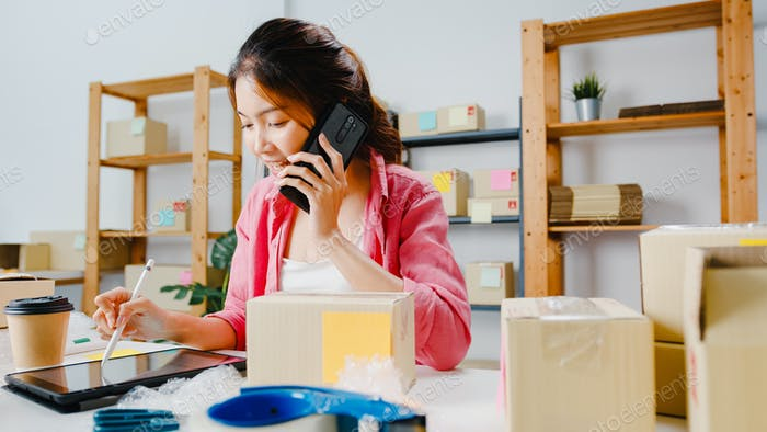 Young Asia businesswoman using mobile phone call receiving purchase order and check product on stock