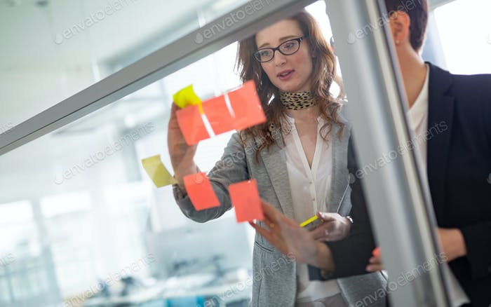 Creative business team looking at sticky notes on window