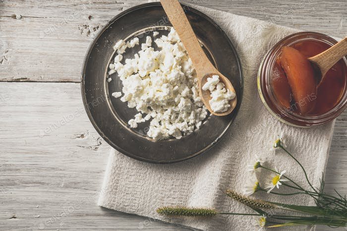Fresh cottage cheese with  jam and flowers on the white wooden table top view