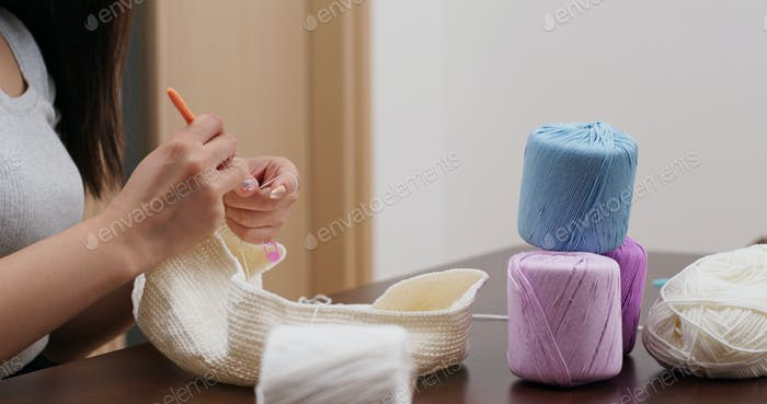 Woman knitting with crochet hook and yarn