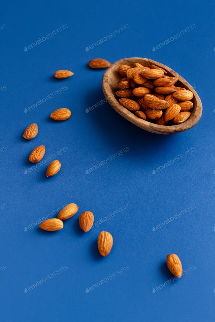 Fresh almonds in a bowl on a blue background