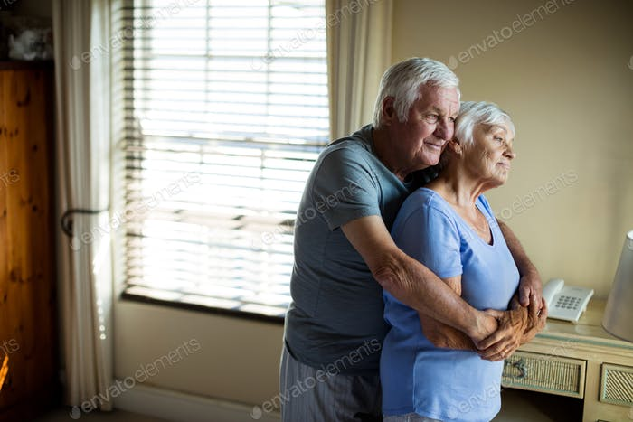 Senior couple embracing each other in the bedroom