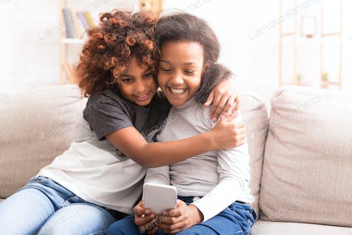 Preteen Mädchen mit Smartphone, verbringen Zeit zusammen