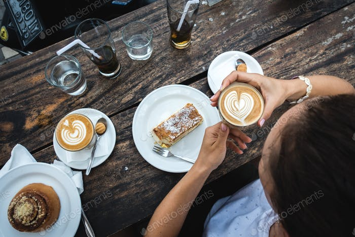 Girl treating herself with great coffee and cake