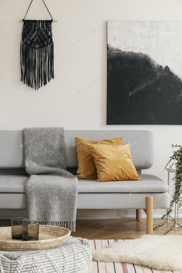 Brown pillows and blanket on grey sofa in natural living room in