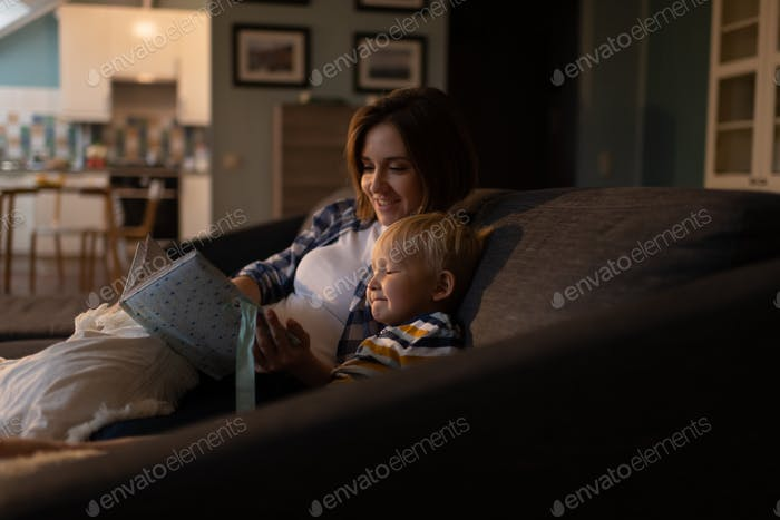 Mother reading bedtime story for little son at home