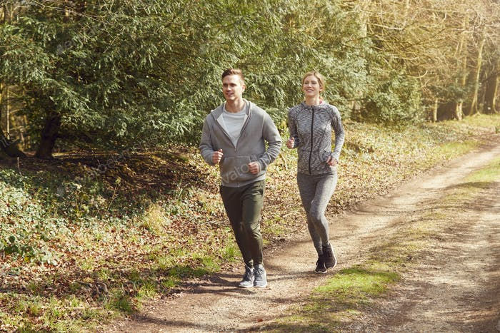 Couple Exercising In Autumn Countryside During Covid 19 Lockdown