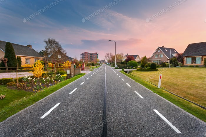 Landscape with asphalt road through the town at sunset