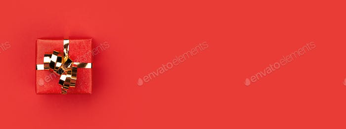 Banner with Red Gift Box Tied Golden Bow on Red Background.