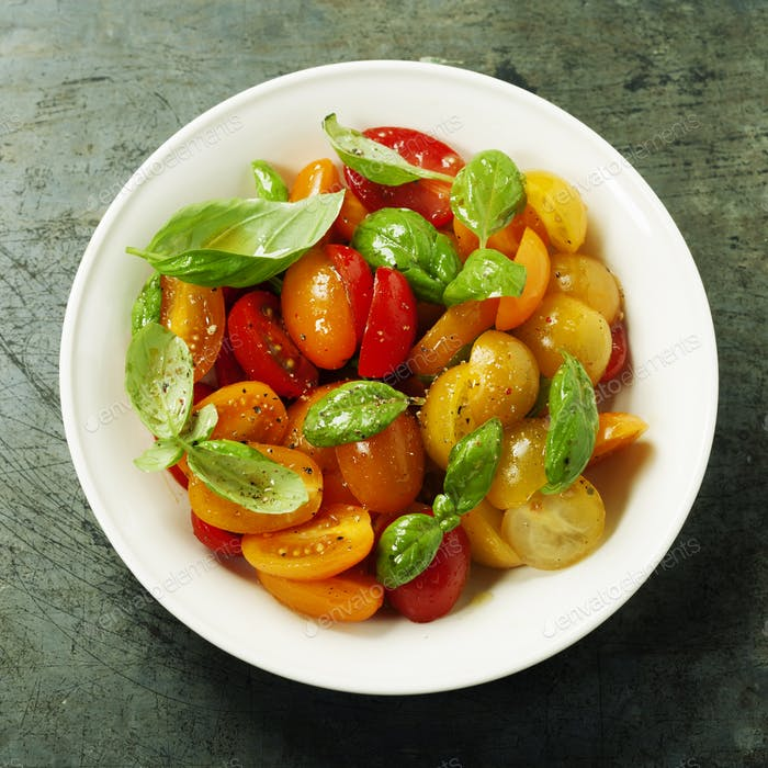 Frische Tomaten mit Basilikumblättern in einer Schüssel