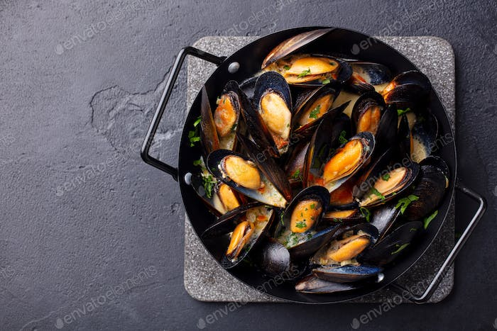 Mussels With Herbs and Sauce in Black Pan. Dark Background. Copy Space. Top View.
