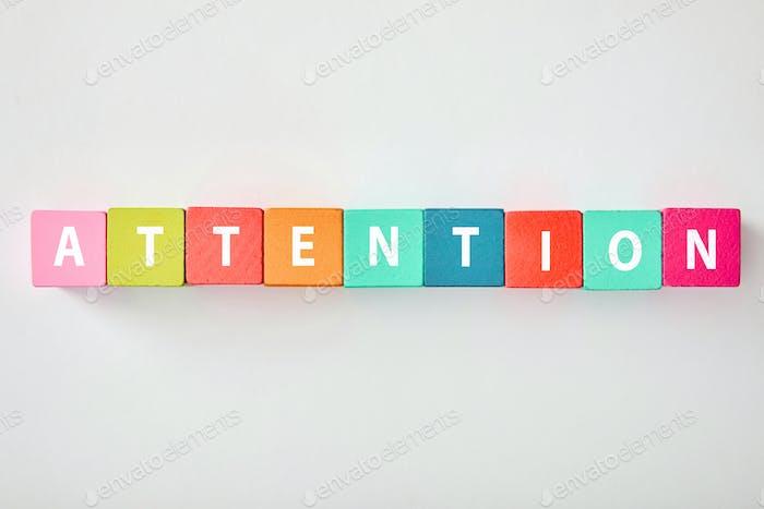 Draufsicht auf Aufmerksamkeitsbeschriftung aus bunten Blöcken auf grauem Hintergrund