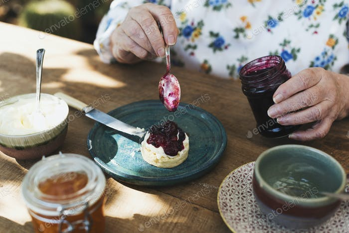 Woman putting blueberry jam on a scone