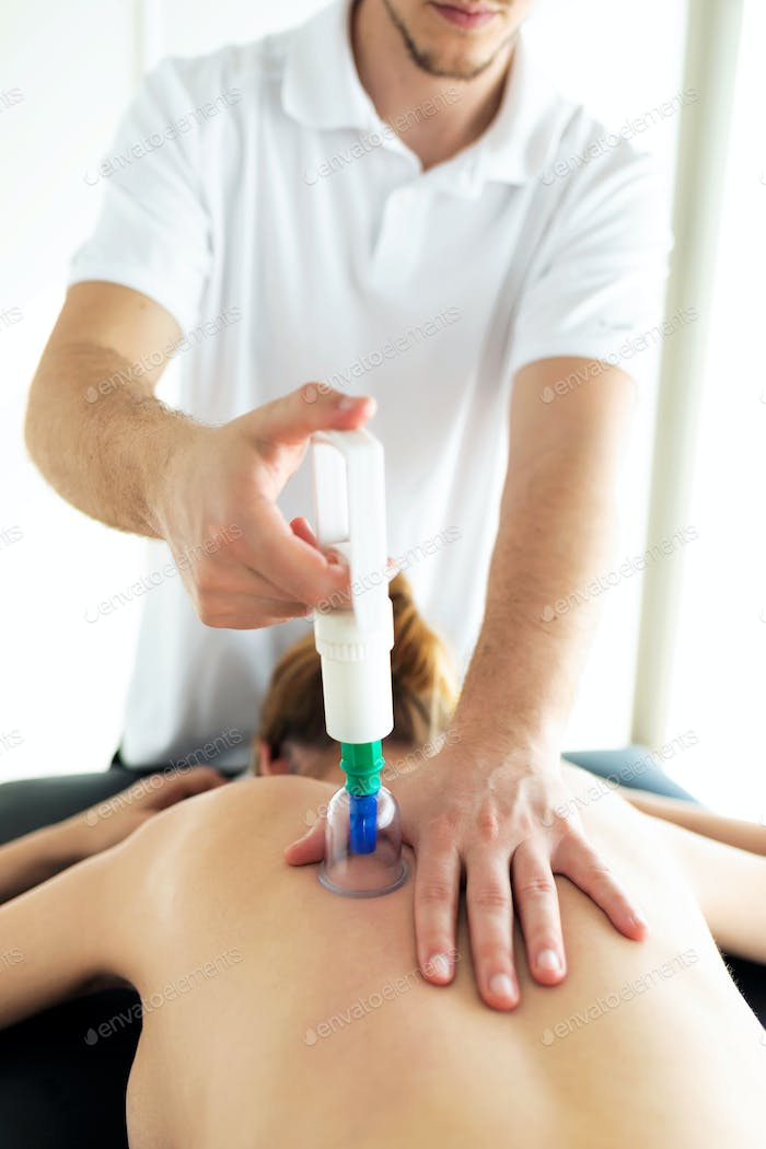Physiotherapist applying cupping treatment to the patient in a physiotherapy room.