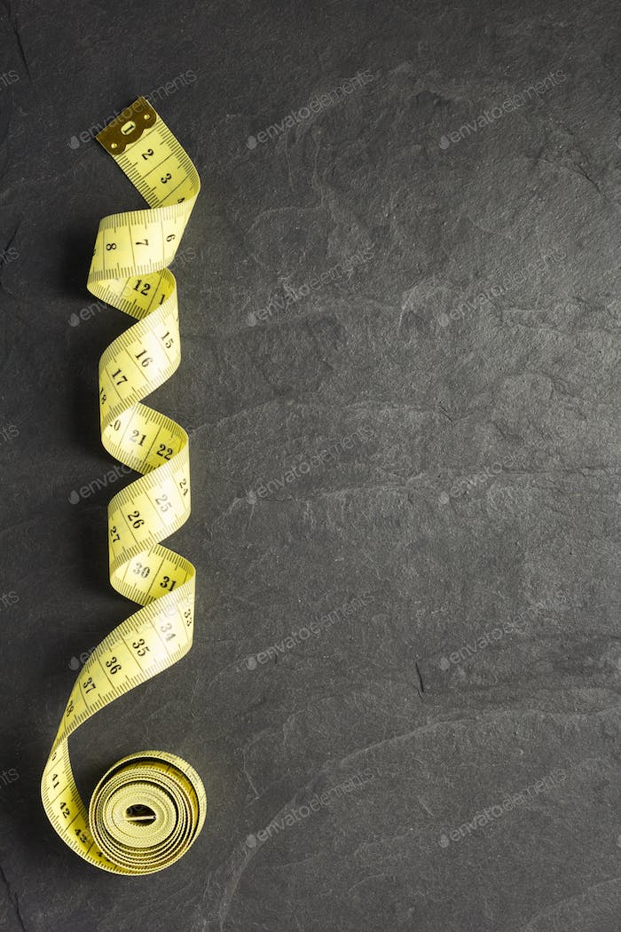 tape measure on slate stone background