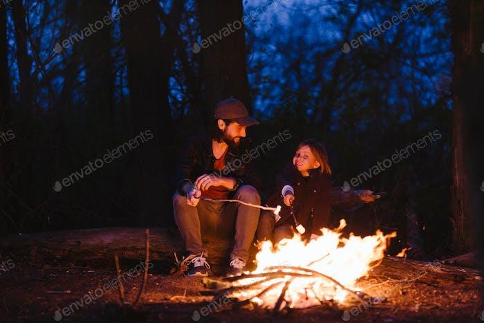Der Vater und sein Sohn sitzen auf den Baumstämmen im Wald vor einem Feuer und braten