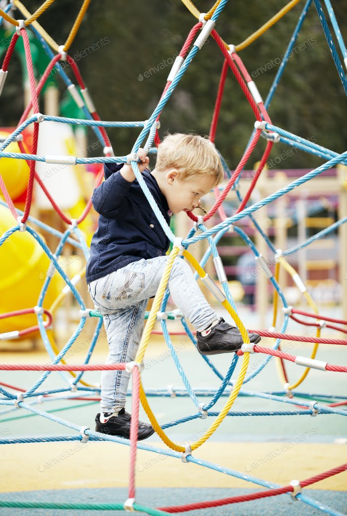 Happy little boy climbing on playground equipment