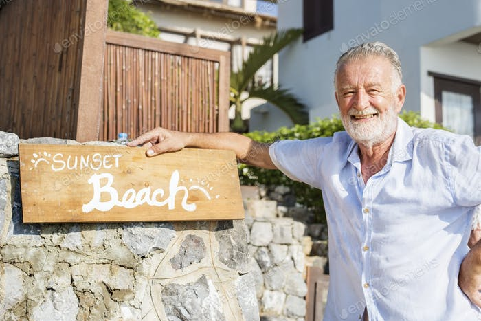 Mature man standing by a resort sign
