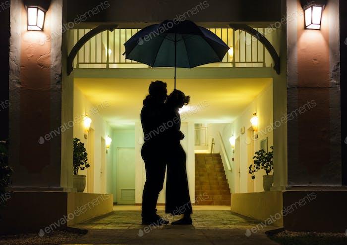 Couple in silhouette Kissing Under Umbrella