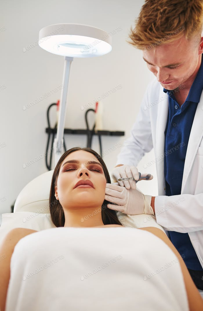 Young male doctor performing botox injections on a female client