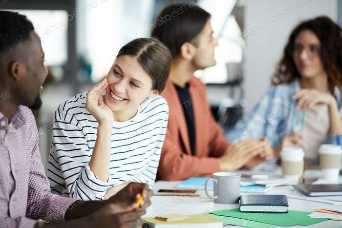 Young Woman Talking to Colleague in Meeting