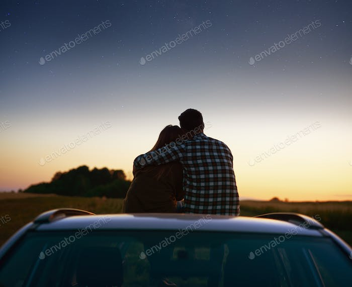 Rear view of loving couple enjoying the view at night