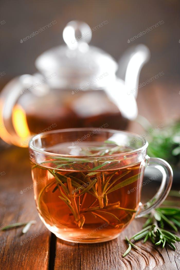 Rosmarin Tee in Glas Teetasse auf rustikalem Holztisch Nahaufnahme. Kräutervitamintee