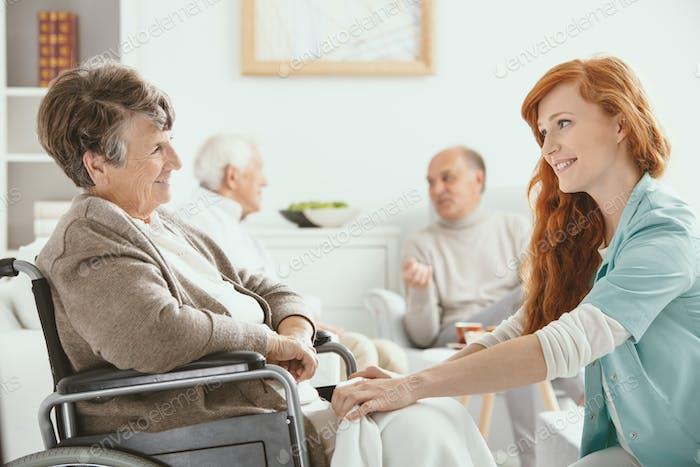 Redhead smiling nurse helping senior patient in hospice
