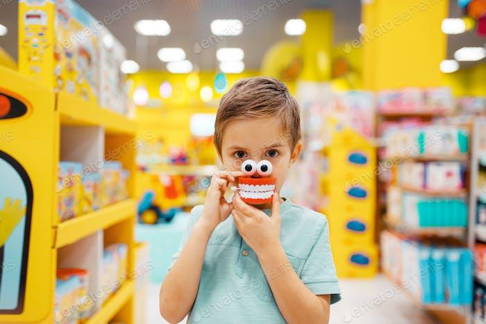 Junge hält Kieferspielzeug im Regal im Kinderladen