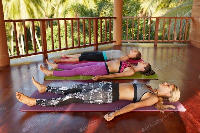 Yoga class with women lying on floor , Savasana