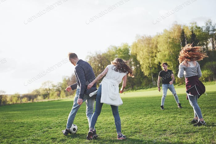 A group of friends in casual outfit play soccer in the open air. People have fun and have fun