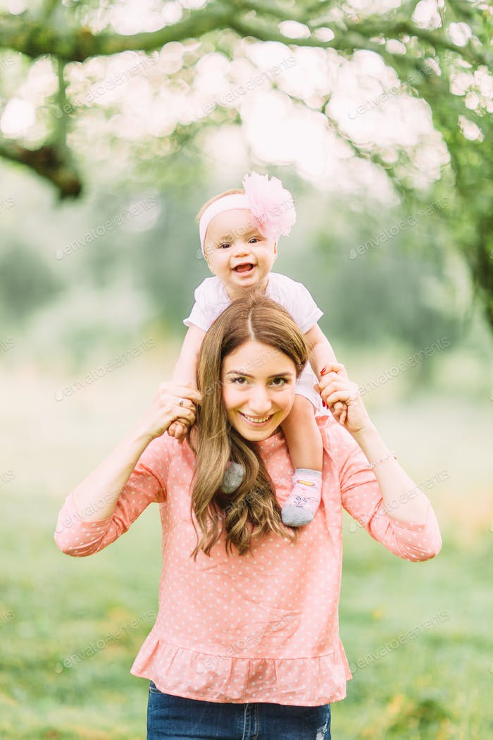 Mother and little daughter playing together in a park. Happy cheerful family. Mother and baby