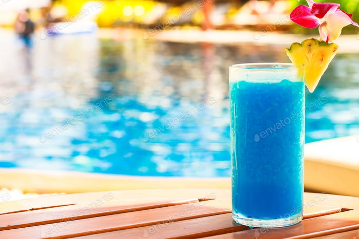 Tropical blue cocktail on woodem table near swimming pool