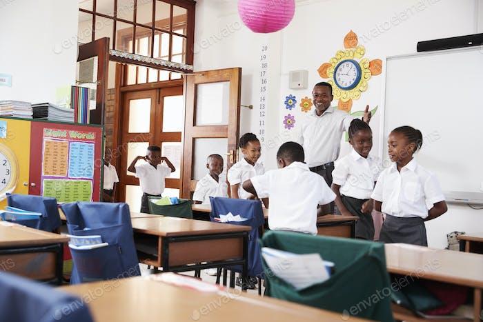 Lehrer begrüßt Kinder, die in der Grundschule kommen